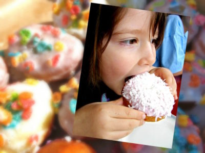 Child eating a donut that is covered with icing and coconut.